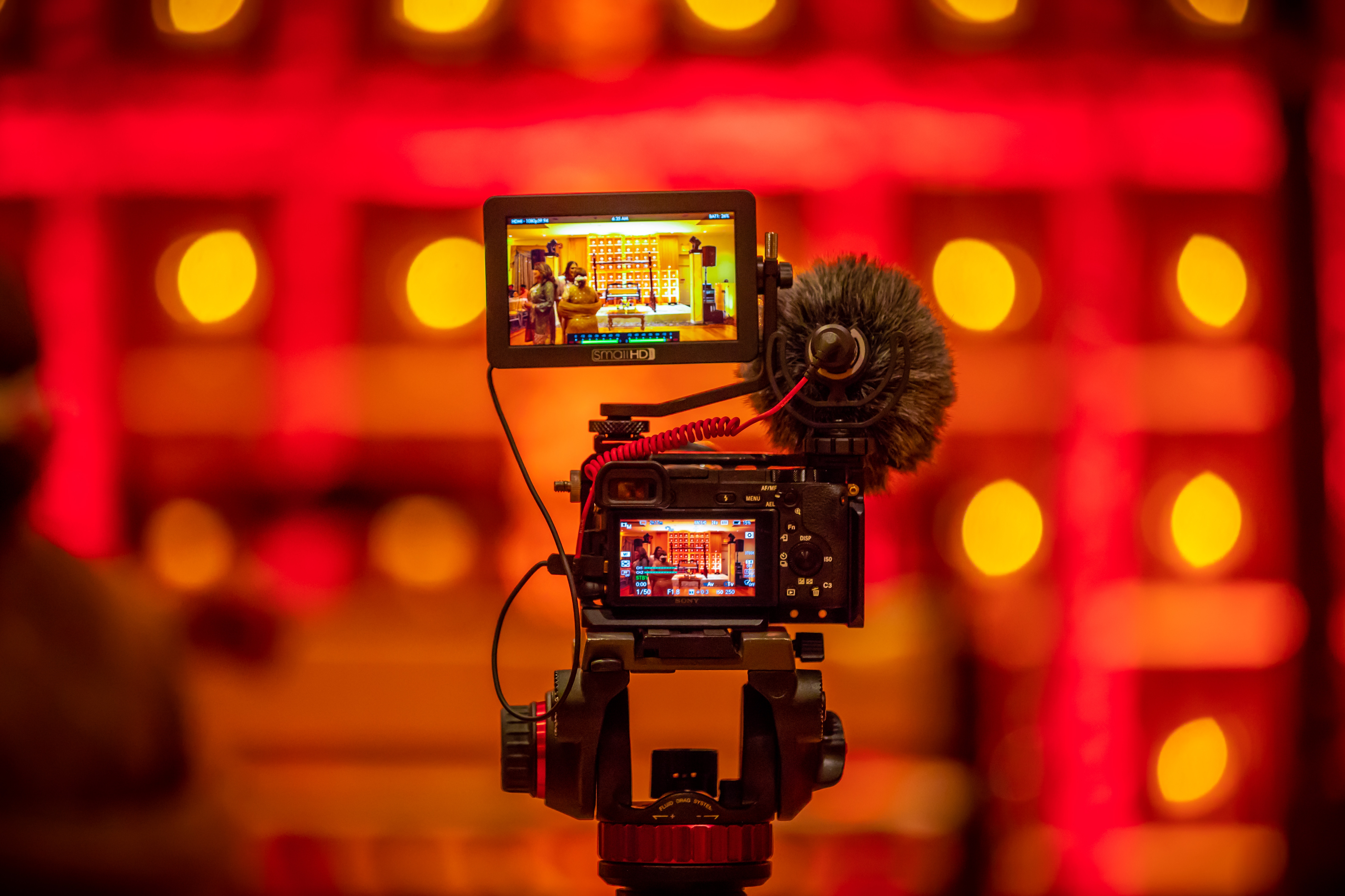digital video camera set up with red lights in the background, capturing digital video for marketing content